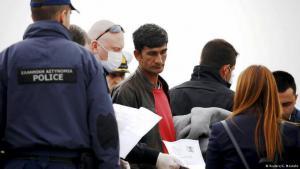 لاجئون في أوروبا يحملون أوراقهم بأيديهم لدى السلطات