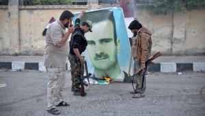 عناصر من جبهة النصرة عند صورة للأسد في إدلب. Foto: Getty Images/AFP/O. Haj Kadour