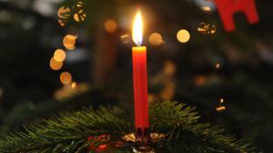 شمعة مشتعلة على غصن شجرة من أشجار عيد الميلاد.Foto: Fotolia/lunaundmo