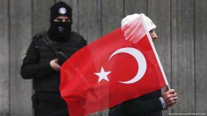 رجل يحمل العلم التركي ويمشي ماراً برجل أمن يحرس المحل الليلي الذي وقع عنده هجوم إرهابي ليلة رأس السنة 2017. (photo: picture-alliance/AP Photo/E. Gurel)
