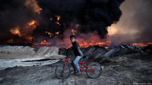 """صبي عراقي على دراجته وهو يمر بحقول نفط محترقة جراء قصف """"داعش"""" في منطقة القيارة قرب الموصل. Foto: Getty Images/C. Court"""