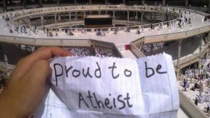"""""""شخص يحمل عند الكعبة في مكة ورقة مكتوب عليها بالإنكليزية: """"فخور بأن أكون ملحداً"""". (source: Twitter)"""