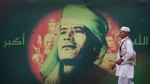 """رجل ليبي من طرابلس في عام 2009 يمر إلى جانب صورة للقذافي وإلى جانبها مكتوب """"الله أكبر"""". Quelle: AP/Ben Curtis"""