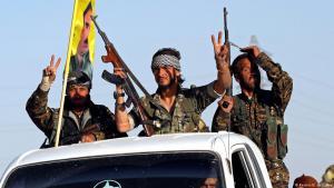 يرفع مقاتلو قوات سوريا الديمقراطية أيديهم بعلامة النصر في الوقت الذي يمرون فيه عبر مدينة عين عيسى الصغيرة باتجاه الرقة.
