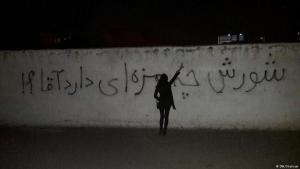 """امرأة إيرانية أمام جدارية مكتوب فيها: """"ما هو طعم الثورة [الانتفاضة]، يا سيدي؟!"""" (في إشارة إلى """"آية الله خامنئي"""" في إيران). Foto: DW"""