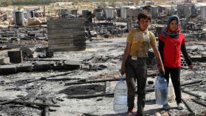 صورة أرشيفية مؤرخة في 9 أغسطس / آب 2014 تظهر طفلين سوريين من اللاجئين يحملون زجاجات مياه أثناء سيرهم وسط الأضرار وبقايا خيام للاجئين السوريين التي أُحرِقَت في القتال بين جنود الجيش اللبناني ومتشددين إسلاميين في بلدة عرسال الحدودية السنية، في وادي البقاع الشرقي في لبنان. (photo: Reuters/Ahmad Shalha)