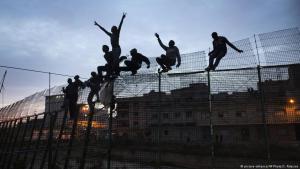 لاجئون يجتازون سياج مليلية من المغرب إلى إسبانيا عام 2017. Foto: picture-alliance/AP Photo/S. Palacios