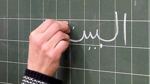 كتابة عربية بالطباشير على لوح سبّورة. Foto: dpa