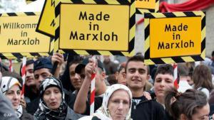 """إبان افتتاح مسجد جديد في مدينة دويسبورغ في حي ماركسلوه في ألمانيا، أتراك يحملون لافتات مكتوب عليها """"صُنِعَ في ماركسلوه"""" في تاريخ 26 / 10 / 2008. (photo: AP Photo/Martin Meissner)"""