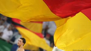 مسعود أوزيل وفوقه علم ألمانيا. (photo: picture-alliance/dpa/R. Vennenbernd)