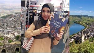 هدى الجندي مع كتابها في معرض فرنكفورت للكتاب. وفي الصورة بلدة والديها في سوريا وبلدتها في ألمانيا. (photo: private)