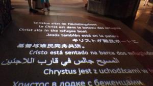 """وُضع قارب صغير في كنيسة كولونيا الشهيرة وكتب عليه باللغات العربية والإنكليزية والفرنسية والفارسية: """"المسيح يجلس في قارب اللاجئين"""". الصورة: منصور حسنو."""