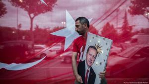 مواطن تركي يرفع صورة الرئيس التركي. هل من مستقبل أردوغان السياسي على المحك بعد الانتخابات البلدية؟