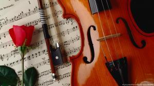 صورة رمزية - آلة كمان موسيقية ووردة وورقة مكتوب عليها نوتات موسيقى كلاسيكية.