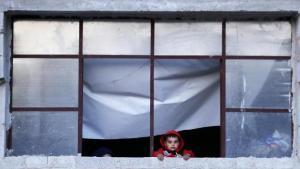 طفل سوري من النازحين من الغوطة الشرقية مع أسرته يطل بوجهه من نافذة ملجأهم في قرية هورجيلي بريف دمشق، سوريا، 13 نيسان (أبريل) 2018 (photo: picture-alliance/AP Photo/H. Ammar)
