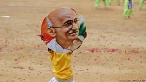 صبي هندي يحمل صورة المهاتما غاندي في بنغالور - الهند. Foto: dpa/AP/A.Rahi