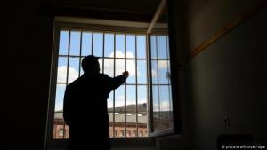 سجين يقف في زنزانة سجن في خلف قضبان نافذة.  Foto: picture alliance/dpa