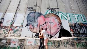 رسم على حائط في القدس - قبلة بين الرئيس الأمريكي دونالد ترامب ورئيس الوزراء الإسرائيلي بنيامين نتنياهو.  (photo: Getty Images/AFP/M.A. Shaers)