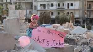 """الطفلة سما واقفة على أنقاض في حلب عام 2016 وهي تحمل ملصقًا كُتِبَ عليه: """"هذه حلب. ما هي العدالة؟"""".  Quelle: """"For Sama""""/Waad al-Kateab"""