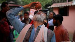 هندي هندوسي يشرب بول البقر خلال فعالية نظمتها مجموعة دينية تروج لشرب بول البقر كعلاج لفيروس كورونا الجديد في نيودلهي - الهند. (photo: picture-alliance/AP Photo)