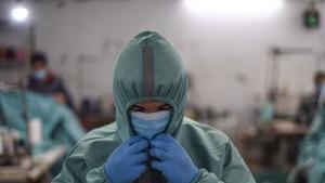 عامل فلسطيني في مصنع ملابس محلي يحاول ارتداء بدلة واقية تم إنتاجها في المصنع ليستخدمها العمال في مواقع مختلفة في ظل انتشار فيروس كورونا - غزة 13 / 03 / 2020.  (photo: ICRC/Abed Zagout)