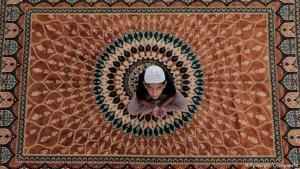 الصلاة في الهواء الطلق في سريلانكا: حتى وإن أُغلقت المساجد يستطيع الناس الصلاة والتعبد في منازلهم، لكن هذا الطفل السريلانكي فضل أن يصلي في الهواء الطلق على سطح إحدى البنايات في مدينة كولومبو. ونرى الطفل في الصورة على سجادة الصلاة، متوجهاً إلى السماء بالدعاء إلى حين حلول موعد الإفطار.