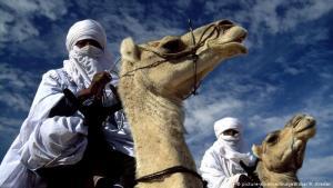 """عمامة وحجاب شرط للعيش في الصحراء الليبية: الطوارق فرع من مجموعة أمازيغية أكبر، ينتشرون في العديد من البلدان، وقد استقر العديد منهم الآن في مناطق محددة وتوقفوا عن حياة الترحال. يطلقون على أنفسهم """"إماجغن"""" في النيجر، واسم """"إموهاغ"""" في الجزائر وليبيا، وإيموشاغ في مالي. أما في اللغة الأمازيغية فيسمون بـ """"طارقة""""."""