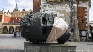 الفن في زمن الكورونا: نرى في الصورة تمثالا بمدينة كراكاو في بولندا للنحات إيغور ميتوراج، الذي قرر أن يحمي تمثاله من خطر فيروس كورونا بهذه الكمامة العملاقة.