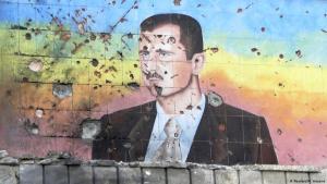 صورة رئيس النظام السوري بشار الأسد مرسومة على جدار وعليها ثقوب يبدو أنها احتجاجية على حكمة.