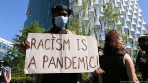"""متظاهر في وسط العاصمة البريطانية لندن يرفع شعار """"جائحة العنصرية"""""""