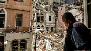 رجل ينظر من نافذة شقته المتضررة في وسط بيروت إلى الدمار الناجم عن الانفجار في مرفأ بيروت 14 / 08 / 2020 - لبنان.  (photo: picture-alliance/dpa/M. Naamani)