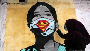 شابة فلسطينية ترسم على الجدار امرأة مرتدية لكمامة واقية من فيروس كورونا.  Foto: Mahmoud Ajjour/Zuma Press/imago/Images