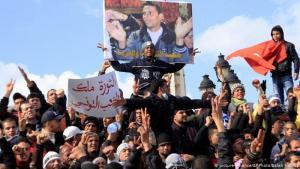 """شرارة """"الربيع"""" على يد بائع متجول: شاب في عمر الـ 26 سنة، يقرّر الاحتجاج على مصادرة عربة الخضراوات التي كان يعيش منها، لكن رفض المسؤولين الاستماع له قاده إلى إحراق نفسه يوم 17 ديسمبر/كانون الأول 2010. توفي لاحقا محمد البوعزيزي متأثرا بالحروق، لكن مدينته سيدي بوزيد تحوّلت إلى شعلة لثورة هائلة هزت كل مناطق تونس وشكلت بداية لاحتجاجات كبيرة في المنطقة العربية."""
