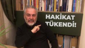 """البروفيسور التركي خبير تفسير القرآن مصطفى أوزتورك وخلفه لوحة مكتوب عليها عبارة تركية ترجمتُها: """"لقد أُرهِقَتْ الحقيقة"""" أو """"لقد اُستُنفِدَتْ الحقيقة"""". (screenshot: YouTube)"""