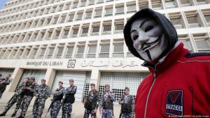 """استمرار الاحتجاجات في لبنان: متظاهر يرتدي قناع """"بانديتا"""" يقف أمام مصرف لبنان المركزي في بيروت"""
