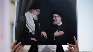 امرأة تحمل صورة، فيها: رئيس إيران المتخَب الجديد إبراهيم رئيسي 2021 ومرشد الثورة الإسلامية آية الله علي خامنئي