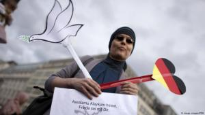 امرأة مسلمة محجبة تحمل قلباً ورقياً بألوان العلم الألماني. Photo: Imago