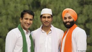 ثلاثة رجال يبتسمون وهم مُرتَدُون ملابس دينية مختلفة - الهند.  flag (photo: Imago/Indiapicture)