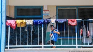 صبي على شرفة ينظر عبر درابزين بلكون عليه ملابس معلقة من أجل التجفيف.  (photo: Mahmoud Khattab/Zumapress/picture-alliance)