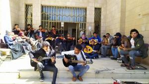فتيان يمنيون وفتيات يمنيات أمام المركز الثقافي في العاصمة صنعاء خلال أداء معزوفة موسيقية في ظل أوضاع الحرب القاسية. Musiker im Jemen - FOTO DW/Safia Mahdi