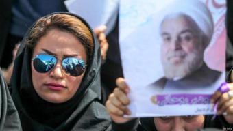 سيدة في طهران تحمل صورة الرئيس روحاني