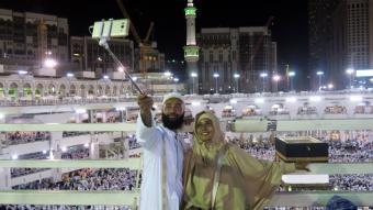 """حاج وحاجة يلتقطان صورة ذاتية """"سِلفي"""" في مكة عند الكعبة. Photo: Reuters"""