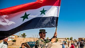 جندي سوري يرفع العلم السوري في شمال سوريا.