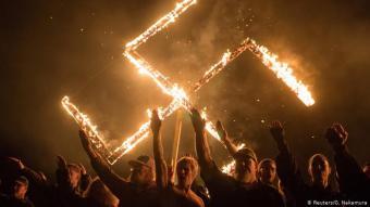 الصليب المعقوف ما زال شعارهم: مجموعة من النازيين الجدد يرفعون الصليب المعقوف وقد توهج فيه اللهيب في نيسان / أبريل 2018.